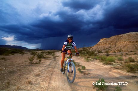 A mountain biker works to outrun a sudden desert downpour near Lajitas.