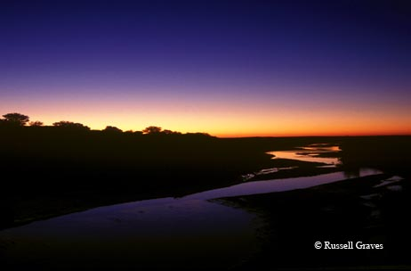 The colors of the sunrise paint the sky, reflected in the Pease River near Paducah.